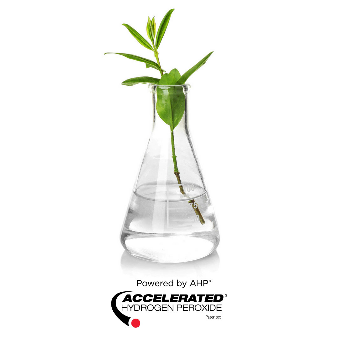 Plant in beaker with Accelerated Hydrogen Peroxide® and AHP® Logos